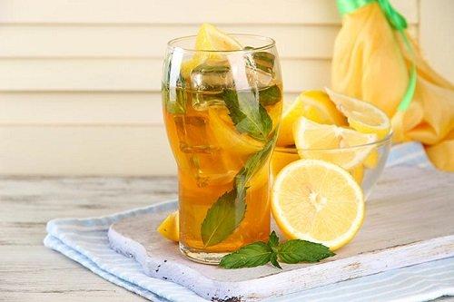 Лимоны и стакан с лимонами и водой